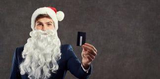 En affärsman med ett skägg i en Santa Claus hatt rymmer en kreditering c arkivbild