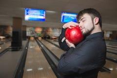 En affärsman med hans ögon stängde en bowlingbunke på bakgrunden av spåren En man spelar bowling Royaltyfria Bilder