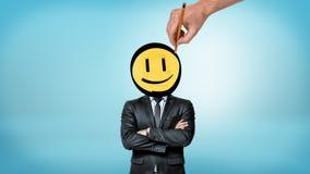 En affärsman med korsade händer står främst sikt, medan en jätte- hand drar en smileyframsida i stället för hans huvud royaltyfri fotografi