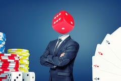 En affärsman med vikta armar står med stor tärning för en kasino i stället för hans huvud royaltyfri bild