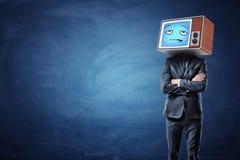 En affärsman med vikta händer och en gammal TV på hans head visning en blå uttråkad emoticon arkivfoto