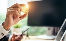En affärsman rymmer en guld- bitcoin arkivbild