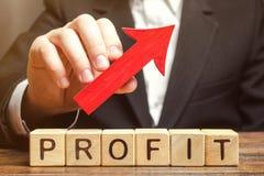 En affärsman rymmer en röd pil upp över träkvarter med ordvinsten Lyckad affär och höga vinster vinst royaltyfri foto
