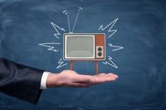 En affärsman` s gömma i handflatan håll en liten retro TV med ben och antennen på svart tavlabakgrund Arkivfoto