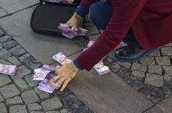 En affärsman samlar pengar från jordningen royaltyfria foton