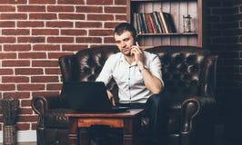 En affärsman sitter på soffan och appellerna från telefonen Rikeman omges av en stilfull inre av rummet royaltyfri fotografi