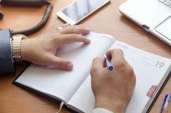 En affärsman skriver i en anteckningsbok Arkivfoto