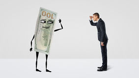 En affärsman som framåtriktat ser på en stor pengarräkning med armar och ben som ser tillbaka på mannen Royaltyfria Bilder