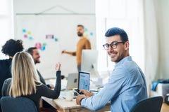En affärsman som ger en presentation till kollegor i ett modernt kontor fotografering för bildbyråer