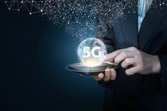 En affärsman som rymmer en apparat med en global översikt och symbolet 5G på det royaltyfria foton
