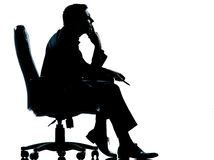 En affärsman som sitter i fåtöljsilhouette Royaltyfria Bilder