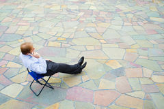 En affärsman som sitter och kallar gatan Royaltyfri Fotografi
