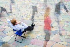 En affärsman som sitter och kallar gatan Arkivfoto