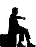 En affärsman som sitter på resväskatid Royaltyfria Bilder