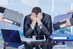 En affärsman stänger hans framsida med hans händer i anfall för arbetespänning arkivfoton