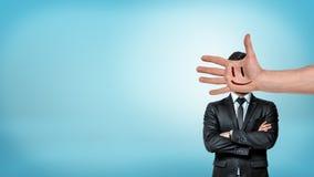 En affärsman står i en främre sikt med vikta armar bak en jätte- manlig hand med en smileyframsida som täcker hans huvud arkivfoton