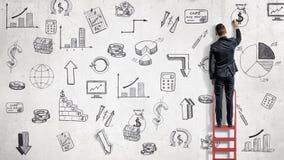 En affärsman står på en röd stege och drar finansiella illustrationer på en stundvägg royaltyfri bild