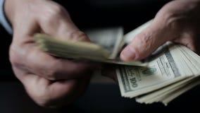 En affärsmans händer som räknar hundra dollarräkningar på en tabell lager videofilmer