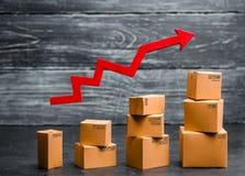 En affärsmans hand rymmer en röd pil upp ovannämnda kartonger vikta gradvist Försäljningar tillväxt och förhöjning i exporter arkivfoto