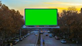 En affischtavla med grön chroma som är nyckel- på bakgrunden av snabba rörande bilar på solnedgången arkivfilmer