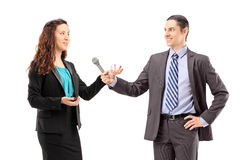 En affärskvinna- och manreporter som har en intervju Arkivfoto