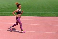 En afrikansk amerikan i sommarsportarna En ung sexig sportig svart flicka kör längs den rosa banan av stadion bredvid royaltyfri bild