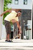 En afrikansk amerikan som upp väljer hans skateboard Arkivbild