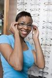 En afrikansk amerikankvinna som försöker på anblickar Fotografering för Bildbyråer
