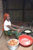 En afrikansk kvinna förbereder stekt bröd Arkivfoton