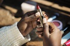 En afrikansk kvinna som använder läppstiftmakeup fotografering för bildbyråer