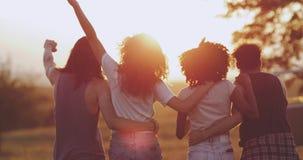 En afrikansk ladie för lockigt hår med hennes vänner som ner går till fältet, fantastiska himmelljus som rymmer sig långsamt lager videofilmer
