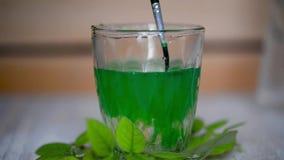 En agua en un vidrio transparente con un cepillo para mezclar la pintura verde Símbolo de la frescura y de la pureza almacen de video
