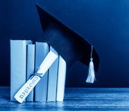 En akademikermössa och en avläggande av examen bläddrar, bundet med det röda bandet, på a royaltyfri fotografi