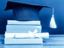 En akademikermössa och en avläggande av examen bläddrar, bundet med det röda bandet, på a arkivfoto
