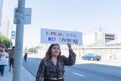 En aktivist rymmer ett tecken under familjerna hör hemma tillsammans mars arkivfoto