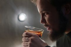En allvarlig grabb med ett skägg rymmer ett exponeringsglas av cola eller whisky med is i hans hand Kontroll som modellerar ljus  royaltyfri bild