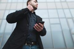 En allvarlig man i en dräkt som går runt om staden med en telefon i hans händer Sikt för lägre vinkel Arkivbilder