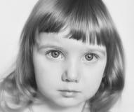 En allvarlig stående av ett gulligt behandla som ett barn flickan i svartvitt Royaltyfri Foto