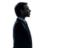 Profilerar den allvarliga ståenden för affärsmanen silhouetten Arkivfoto