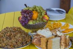 En amarillo la tabla colocaba un cuenco de plov Hay frutas en el florero El pan se corta en pedazos Fotos de archivo
