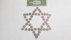 En amerikansk dollarsedel lägger över israeliska sikelmetallmynt som ordnas i en form av judiska sex punkter stjärna royaltyfri bild