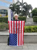 En amerikansk manshow amerikanska flaggan med ord`-TRUMFEN ÄR VÅR TRAGEDI ` På den trådlösa vägen nära USA-ambassaden i Thailand Royaltyfri Bild