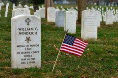 En amerikanska flaggan planteras ?t sidan en milit?rs grav arkivfoton