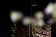 En amerikanska flaggan vinkar högt ovanför ett torn med gotisk arkitektur, med suddiga förgrundsbeståndsdelar fotografering för bildbyråer
