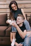 En amor los pares sonríen y tienen té del almuerzo en casa Fotos de archivo libres de regalías