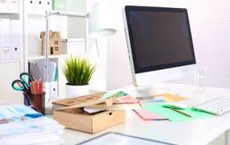 En anmärkningsbok, bärbar dator, penna, pappers- dokument för graf på tabellen för kontorsskrivbord bak vitrullgardinen Royaltyfri Fotografi