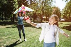 En annan bild av flickan som spelar med draken med hennes mamma Flickan står i en framdel och drar tråden från drake Kvinna royaltyfri bild