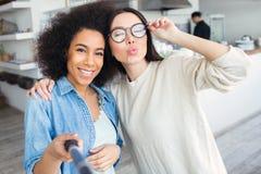 En annan bild av två vänner De gör selfie Flickan i blå skjorta rymmer en selfiepinne och ler till arkivfoto