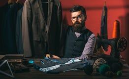 En annan klient sy mekanisering dräktlager och modevisningslokal Skäggigt omslag för manskräddaresömnad affärsklänning royaltyfria bilder