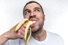 En annan konstig bild av den orakade grabben som äter den mogna bananen Han biter ett stort stycke av frukt Mannen är att tycka o arkivfoton